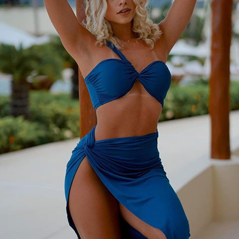 Yaslen Clemente is looking hot in blue bra and skirt and holding a pillar while posing for a picture.