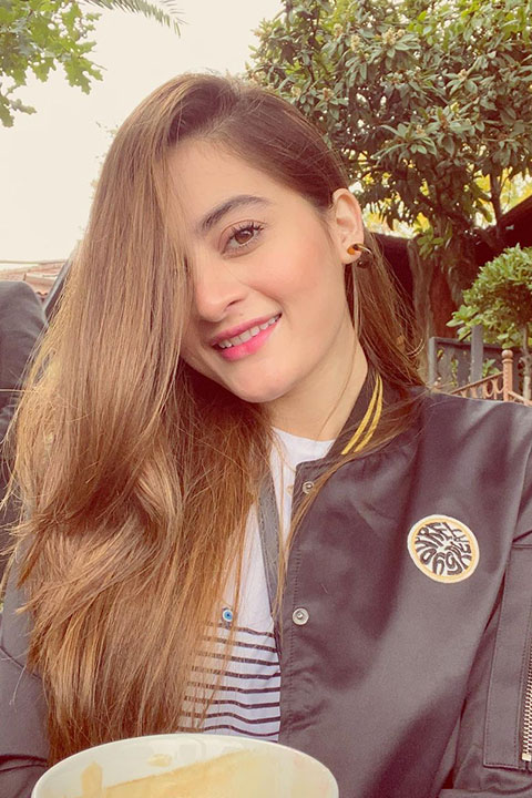 Aimen Khan with blonde hair and black jacket