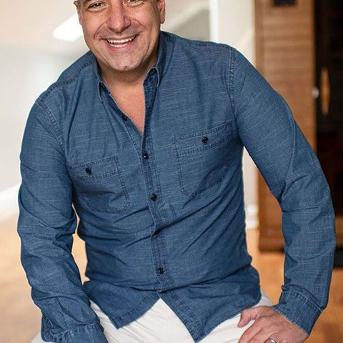 Marc damelio smiling in blue shirt and white cotton jeans