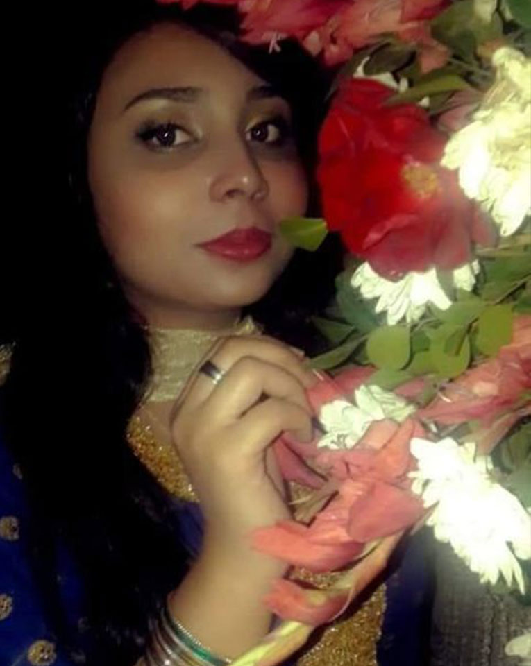 Neha Hussain posing in front of beautiful flowers