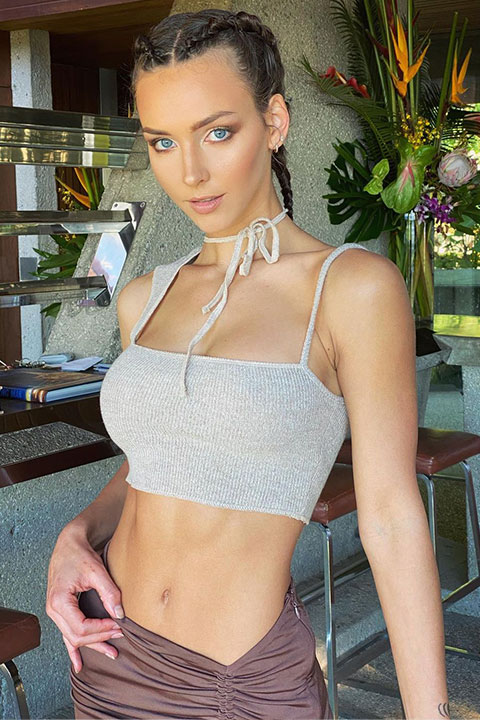 Rachel cook is looking at the camera and posing for a picture in grey blouse .