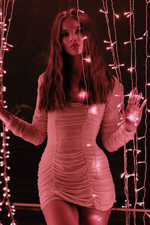Anna Zak is standing behind the hanging lights and looking gorgeous.
