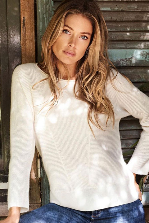 Doutzen Kroes is posing for a picture in white shirt and blue jeans.