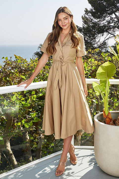 Miranda Kerr is posing for a picture with a smiling face and she is looking beautiful in brown dress.