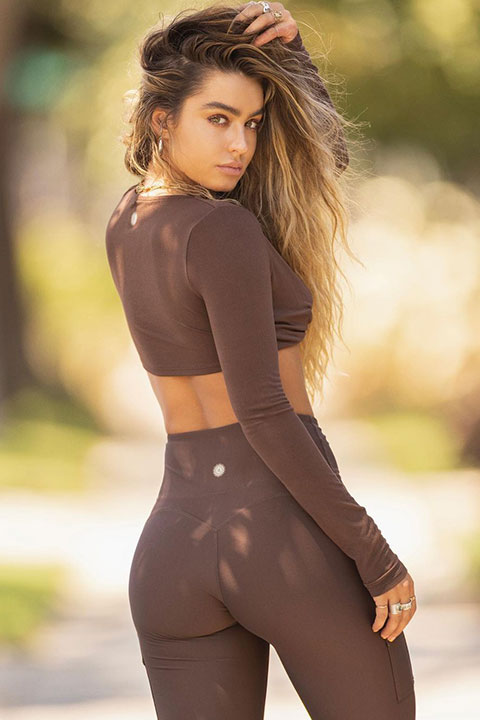 Sommer Ray is looking beautiful in brown blouse and trouser and she hold her hair.